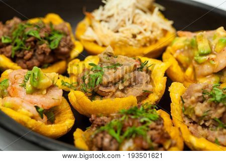 Plantain cups filled with different types of stuffing on black ceramic dish