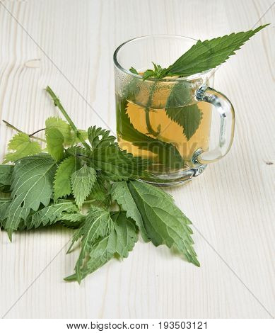 Nettle tea and some of nettle on the wood background leaves in the cup