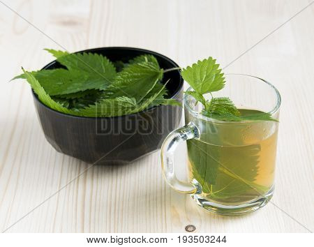 Nettle tea on the wood background leaves in the cup and nettle in a bowl