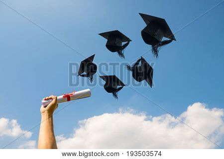 Graduation day Images of hand holding a certificate and Caps or hat throwing in the air with sunshine day on blue sky background Happiness feeling Commencement day Congratulation Ceremony.