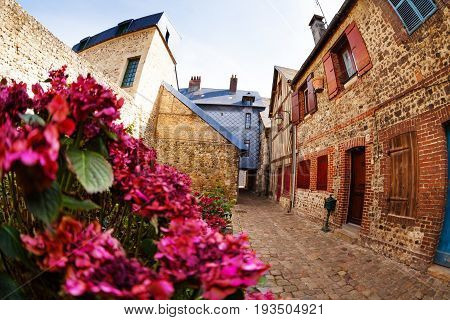 Medieval cobblestone paved street in the old town of Honfleur with houses made out of brick