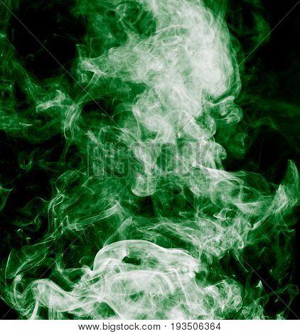 green smoke on a black background . A photo