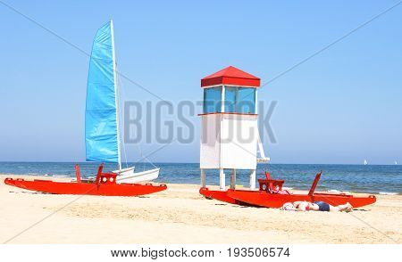 Lifeguard tower red rescue boat on blue sky and ocean background at summer sunny day - Concept of safety in seaside tourism destinations