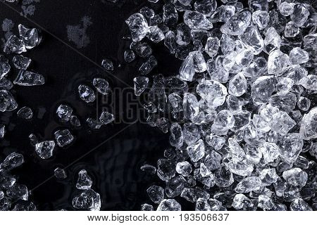 Pieces of crushed ice cubes on black background. Copy space, top view poster