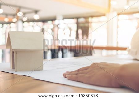 Image of engineer or architectural project Close up of small house model and engineer's hand is laying on BluePrint with Engineering tools on workplace Construction concept.