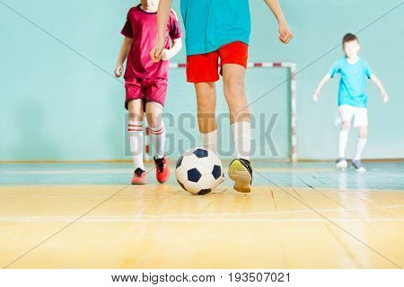 Close-up of football player's legs striking ball  during match in futsal