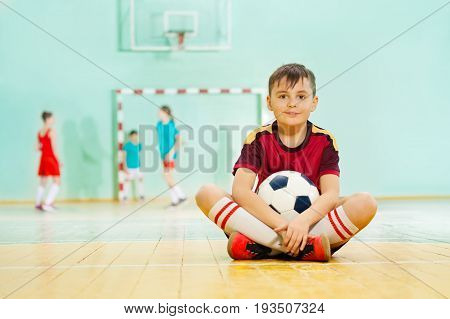 Portrait of 11 years old boy sitting on the floor of school gym with soccer ball