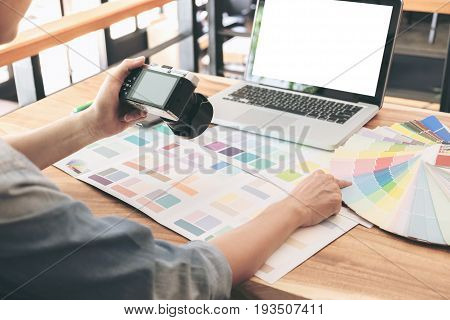 Color samples colour chart swatch sample Graphic designer being selecting Color band and graphics tablet at workplace with work example in camera and laptop on wooden desk.