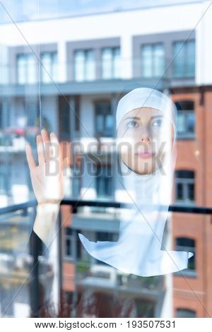 Young Sad Nun Near Window