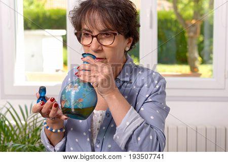 a woman smelling a bottle of liqueur