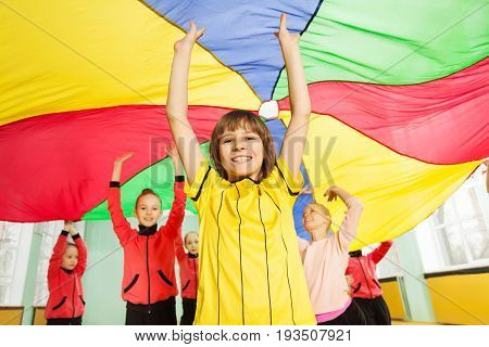 Portrait of smiling preteen boy standing under the canopy made of rainbow parachute with his hands up