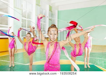 Group of preteen girls wearing pink sparkling leotards, doing rhythmic gymnastics with art ribbon in school sports hall