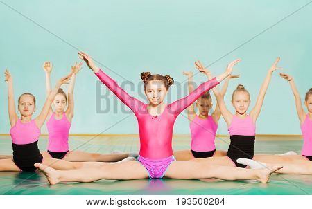Portrait of preteen girls in sportswear performing side splits during gymnastics class, sitting against blanked background