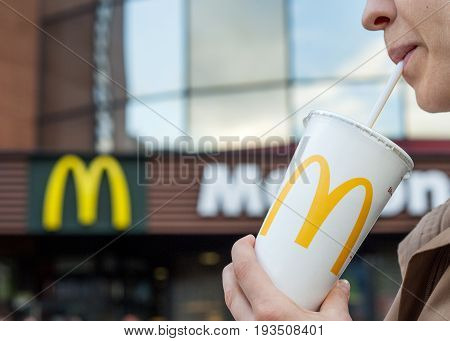 Minsk, Belarus, june 23, 2017: McDonald's soft drink. Woman drinks a drink in the background of the McDonald's restaurant