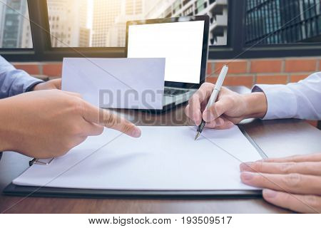 Close up of the hand employer focus the employee to write a letter of resignation and filing final remuneration resign concept.