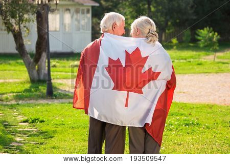 Senior couple and Canadian flag. Two elderly people, back view. Love to homeland.