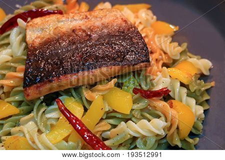Spiral shaped pasta with garlic, dried red chili, yellow pepper and olive oil topped with grilled Salmon
