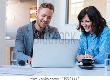 Two smiling work colleagues talking and working together on a laptop while sitting at a table in a meeting room in a modern office