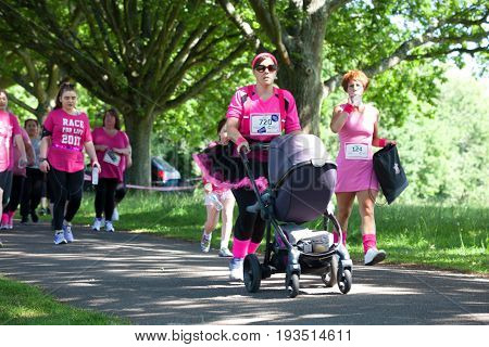 SOUTHAMPTON UK - July 2 2017: Race for Life women run and walk to raise money for Cancer Research charity in Southampton UK. Lady wearing a tutu running with a pushchair.