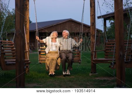 Old couple on porch swing. Man and woman, evening.