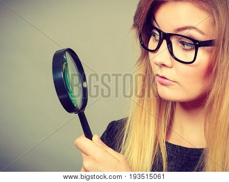 Blonde woman holding magnifying glass investigating something and looking closely trying to find solution.