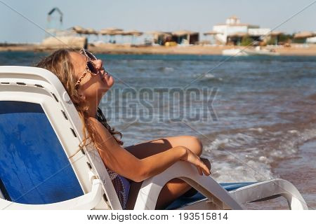 Laughing Young Woman In Sunglasses Sitting In A Deckchair, Against The Background Of The Sea And Tro