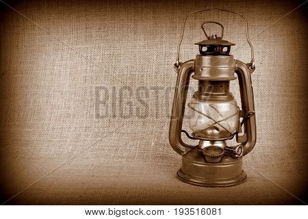 Old oil lamp on burlap and copy space
