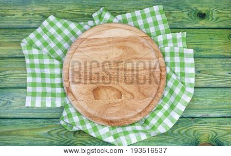 Pizza background. Round Cutting board over green checkered tablecloths on the table, top view