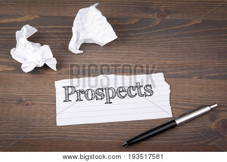 Prospects. paper sheet from the booklet on the wooden table.