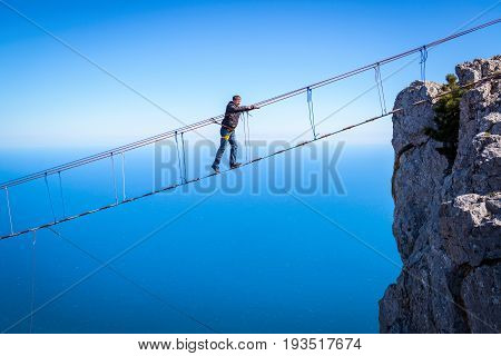 CRIMEA, RUSSIA - MAY 19, 2016: Tourist walking on a rope bridge on the Mount Ai-Petri over the sea. Ai-Petri is one of the highest mountains in Crimea and tourist attraction.