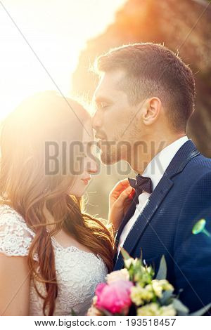 Beautiful couple in love kissing in close-up. Wedding couple kissing at sunset and waves of love and tender feelings. Couple in love on vacation. Wedding ceremony outdoors perfect couple. Blurred