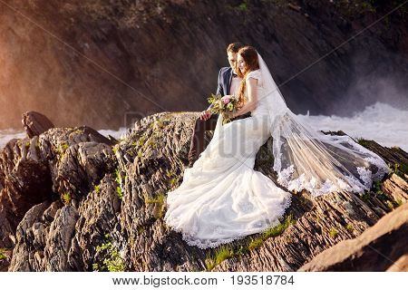 Beautiful couple in love kissing while sitting on the rocks near sea. Wedding couple at sunset and sea love and tender feelings. Loving couple resting. Wedding ceremony outdoors. Perfect couple