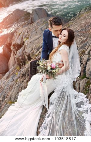 Beautiful couple in love kissing while sitting on the rocks near river. Wedding couple at sunset and rivers love and tender feelings. Loving couple resting. Wedding ceremony outdoors. Perfect couple