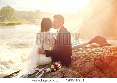 Beautiful couple love kissing while sitting on rocks near river. Wedding couple at sunset and rivers love and tender feelings. Loving couple resting. Wedding ceremony outdoors. Perfect couple blurred