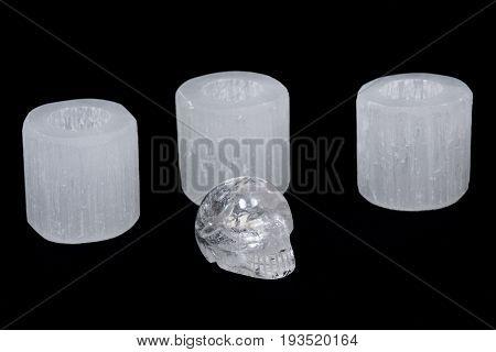 White selenite cylinder tea light holders with clear quartz skull on black background