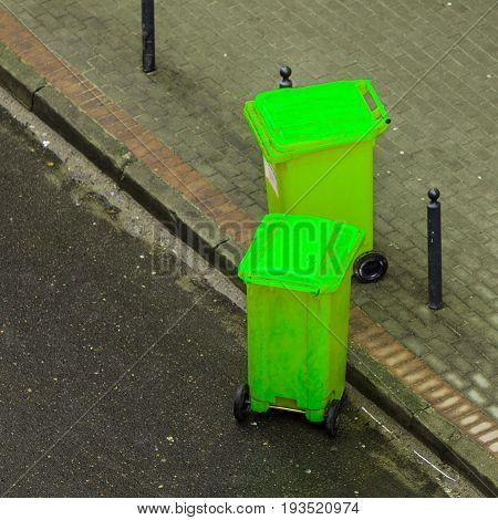 Plastic green wheely bins in the street outside waiting for garbage truck. Top view