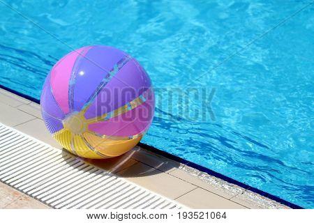 Beachball and swimmingpool. summer close up image