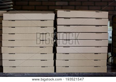 Stack of brown pizza boxes in pizzeria.