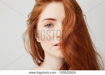 Close up photo of young tender beautiful girl with red hair looking at camera over white background.