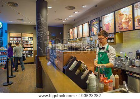 SHENZHEN, CHINA - FEBRUARY 16, 2015: barista at Starbucks coffee shop.