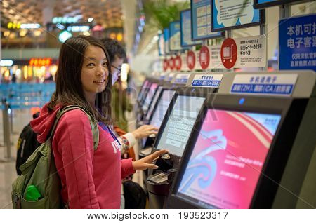 SHENZHEN, CHINA - FEBRUARY 16, 2015: woman use self check-in kiosk at Shenzhen Bao'an International Airport.