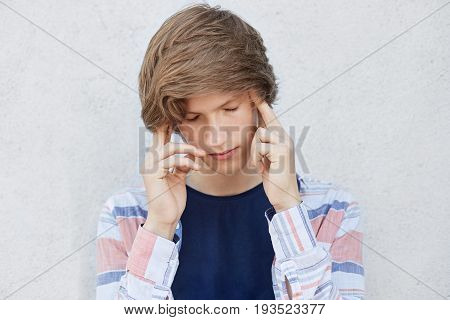 Pensive Concentrated Teenage Boy With Stylish Haircut Looking Down Thinking Over Something Important