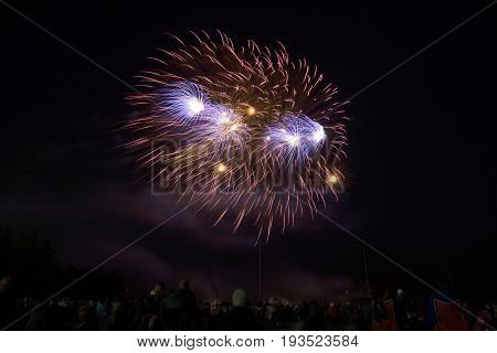 Round Bursts Of Glowing Fireworks High In Sky Over Crowd Of People Below