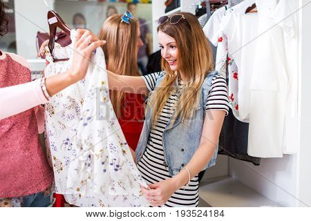 Pretty girl looking excited holding blouse offered by shopping assistant in clothing store.