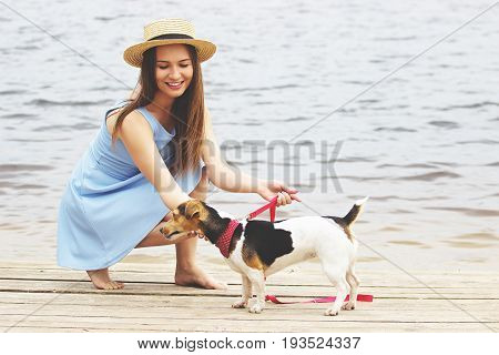 Let's Play, Honey. Horizontal Shot Of Beautiful Young Woman In Dress Playing With Dog And Smiling Wh