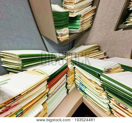 A distorted view of a cubicle desk with stacks of work folders.