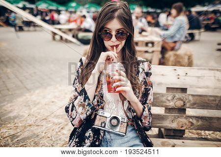 Stylish Hipster Woman Drinking Lemonade. Cool Boho Girl In Denim And Bohemian Clothes, Holding Cockt