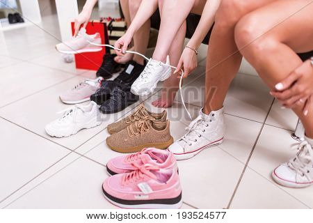 Cropped image of teenage girls trying on sports shoes in a shop.