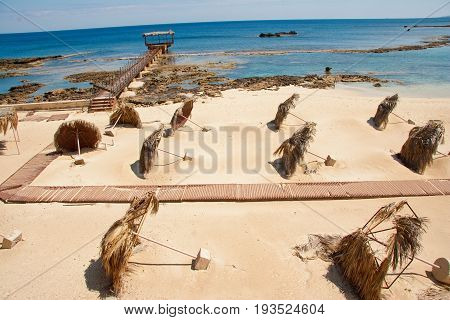 Tilted palm-leaf umbrellas on Constantia sandy beach in Famagusta Cyprus. Photo taken in March 2009