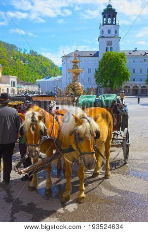Central place in Salzburg city with carriages and horses, Austria